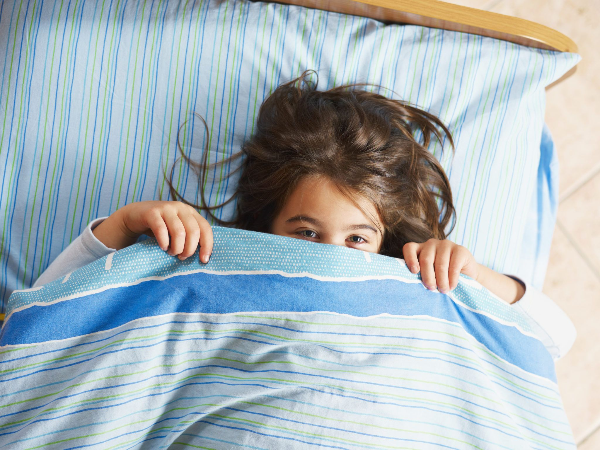 Girl under covers, looking at camera.
