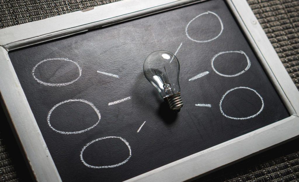 Light bulb resting on a chalkboard