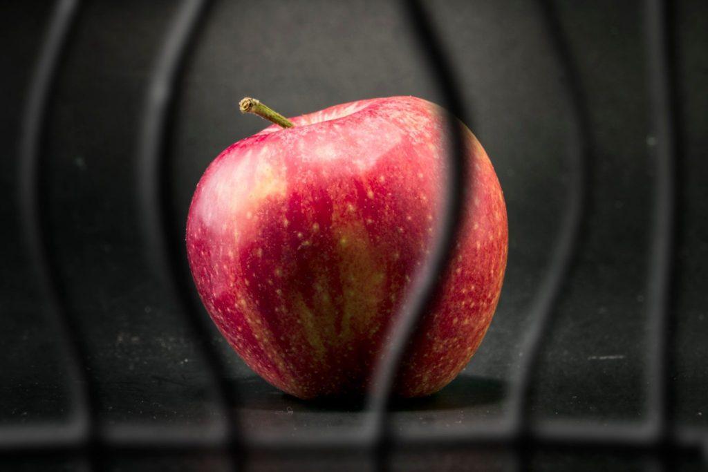 An apple behind prison bars