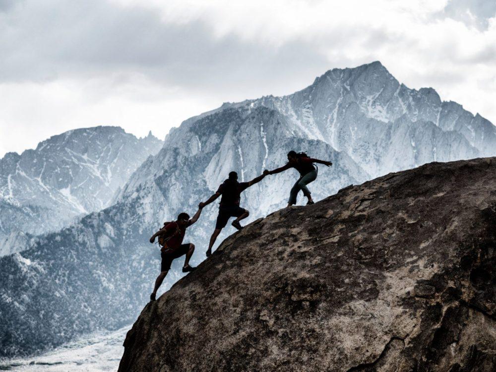 3 men climbing a mountain. All three are helping eachother climb.