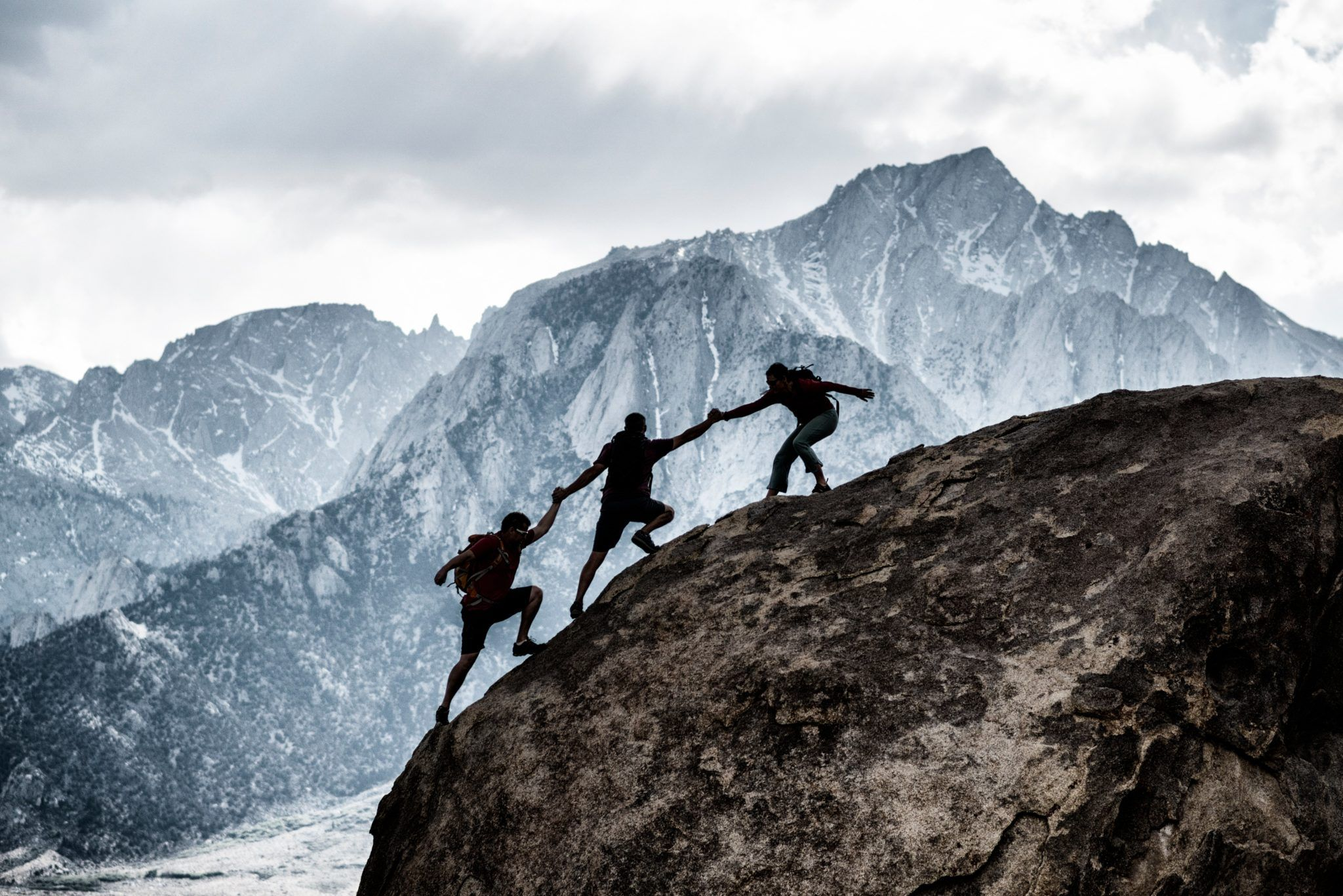 3 men climbing a mountain. All three are helping eachother climb.