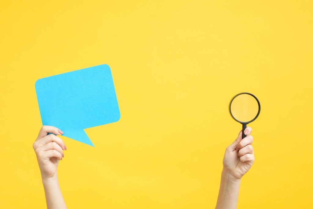 speech bubble and magnifying glass against yellow background