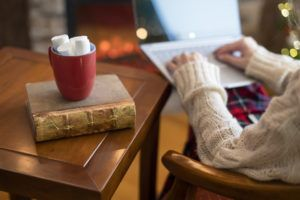 Woman hand with laptop, cup of hot cocoa and marshmallow on book on wooden table near christmas tree and fireplace.