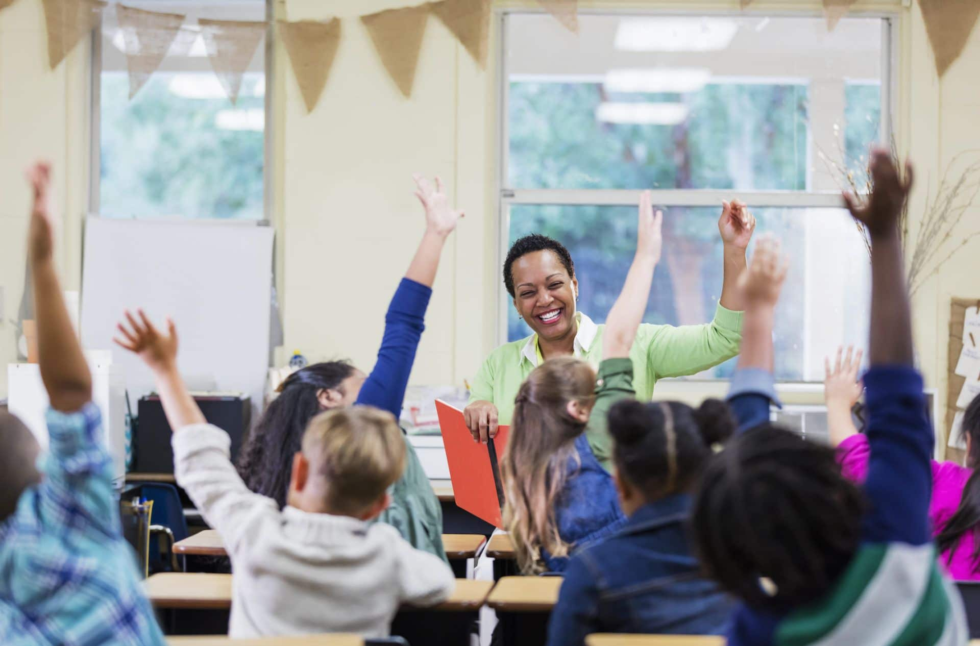 photo of a diverse classroom with students raising hands and teacher smiling